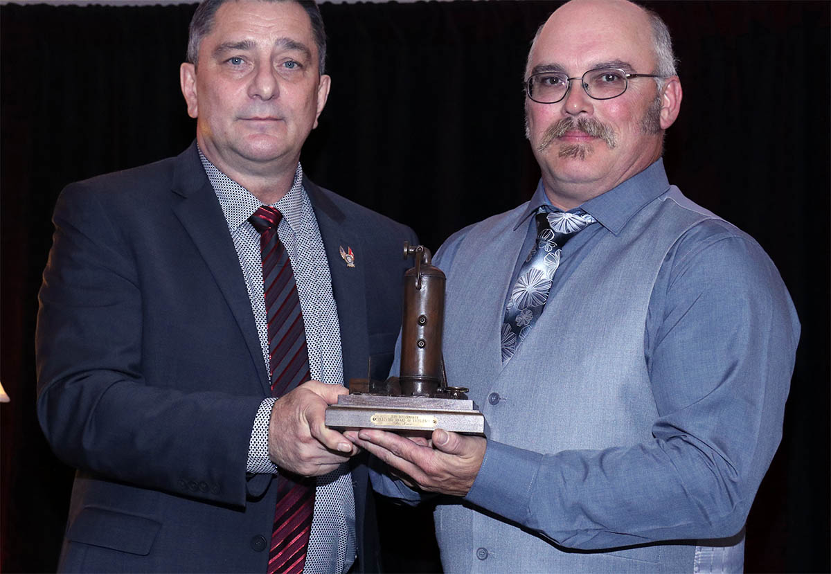 International Vice-President Arnie Stadnick presents Chris Kiwior with the Industry Award of Excellence which he accepted on behalf of his father Joe Kiwior.
